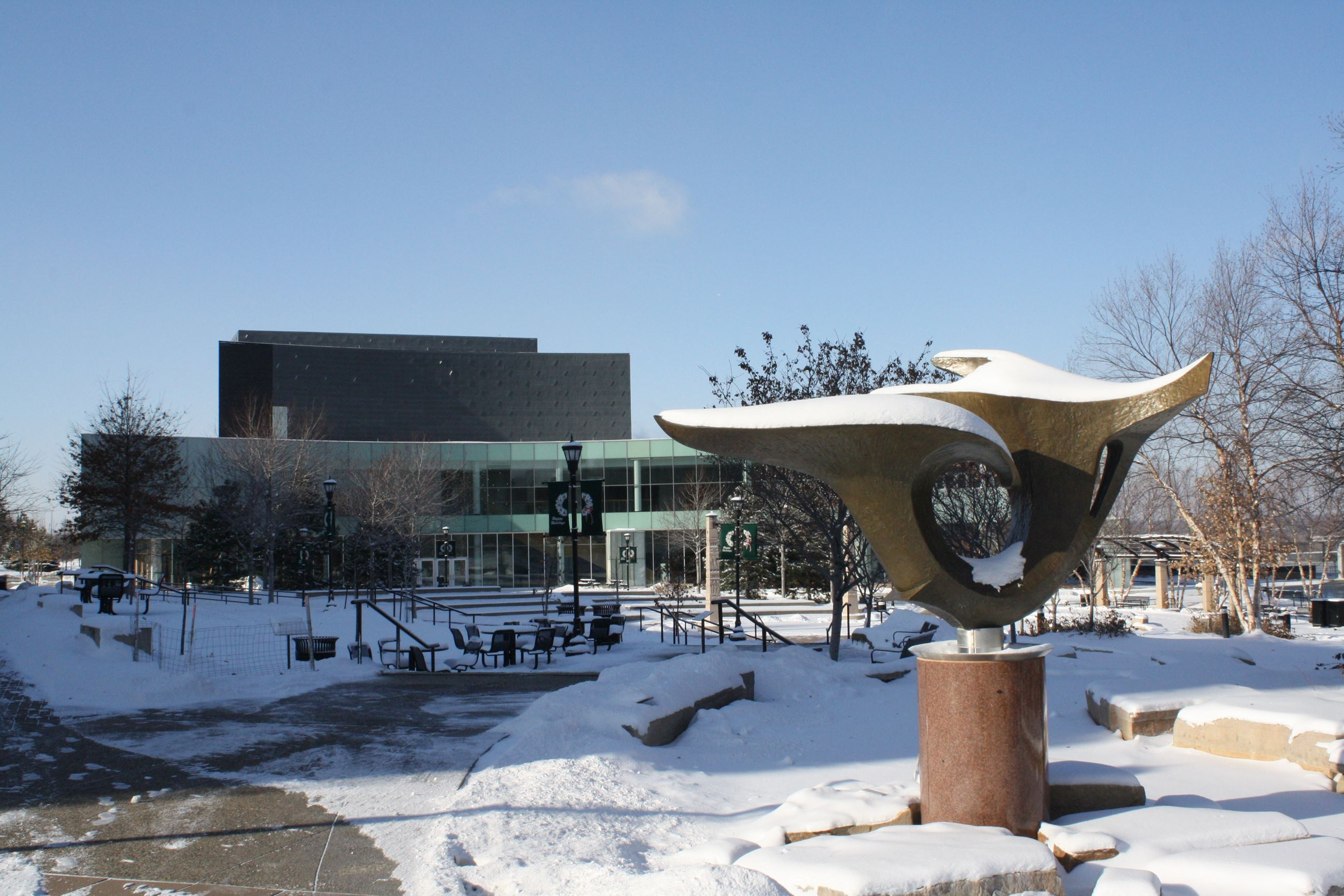 Centrifuge sculpture covered in snow. The Ames Center can be seen in the background