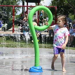 A young girl plays with a sprinkler in a splash pad while water sprays behind her