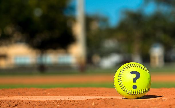 Yellow softball with question mark on dirt field