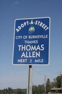 Blue street sign that says Adopt-A-Street. City of Burnsville thanks Thomas Allen. Next 1 mile.